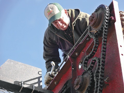 David Rupple fixes a broken chain on a sugarbeet digger